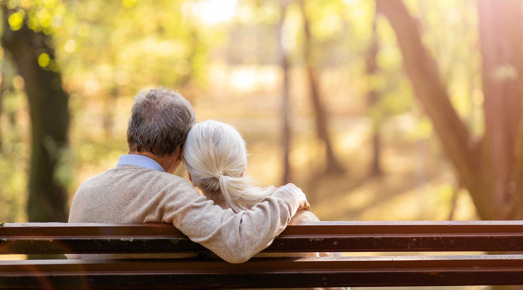 senior man and woman on park bench in the fall