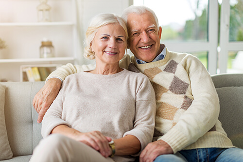 senior couple smiling on a couch