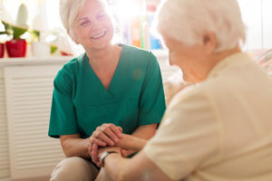nurse sitting with senior woman at Senior Assisted Living homes in florida