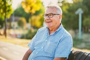 older man sitting on bench outside memory care nursing homes fl