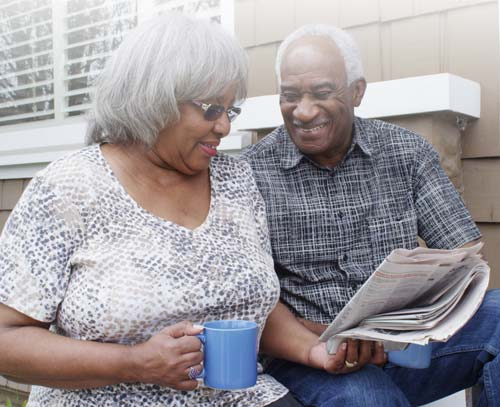 senior couple reading the newspaper at aston gardens tampa bay