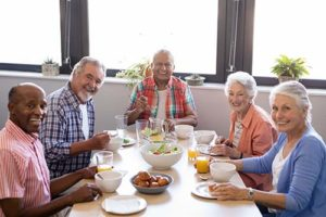a group of people eating while enjoying Venice Florida Senior Living Programs